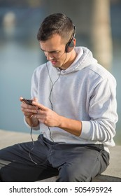Attractive young man is resting after hard workout. He is using his phone while sitting with a towel around his neck and headphones on his ears.