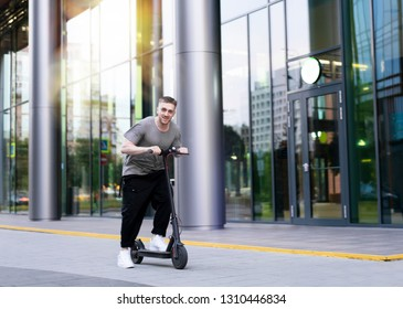 Attractive young man riding a kick scooter at cityscape background.