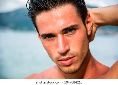 Attractive young man in the sea getting out of water with wet hair, looking at camera