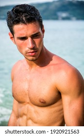 Attractive young man in the sea getting out of water with wet hair, looking away to a side