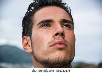 Attractive young man in the sea getting out of water with wet hair, looking in camera