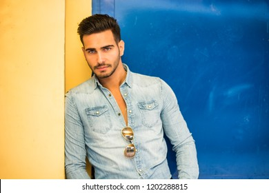 Attractive young man sitting against colorful wall, looking at camera