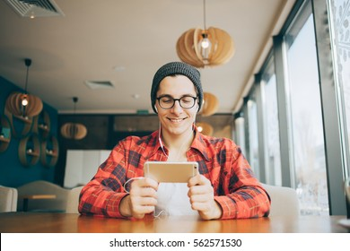Attractive young man is sitting in office and drinking tea. He is holding a mobile phone and watching video or reading interesting article. Handsome guy is smiling