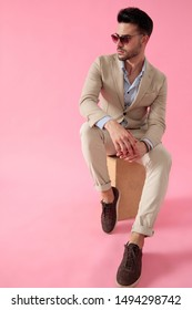 attractive young man sitting on wooden box, wearing a suit and a pair of sunglasses, leaning elbow on knee and  looking to side on a pink background; full body
