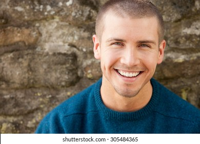 Attractive young man sitting outside. He is smiling at the camera.