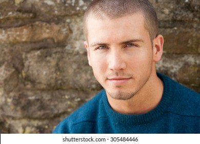 Attractive young man sitting outside. He is looking pensively at the camera.