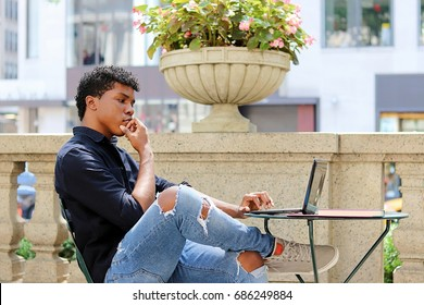 Attractive young man sitting outside working, reading, using laptop