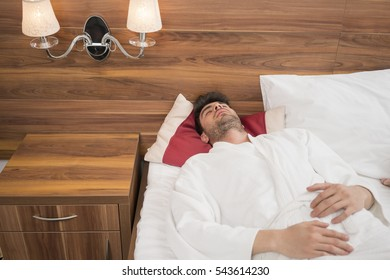 Attractive young man sleeping in badroom