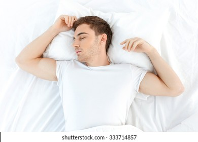 Attractive young man is sleeping in his bed. He is lying in his bed with relaxation