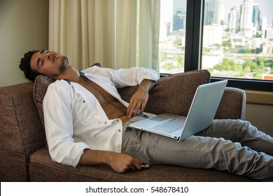 Attractive Young Man Sleeping While Working on his Start-up Business Reclining Comfortably with Laptop on Chaise Longue Working - Young Male College or University Student Doing Homework, in Bedroom