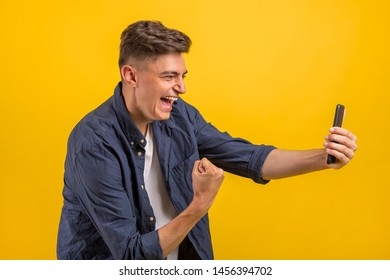 Attractive young man with smartphone on color yellow background. Portrait of an excited young man looking at mobile phone isolated over yellow background, celebrating