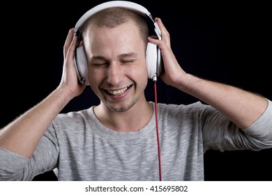 attractive young man smiling and listening to music on headphones with closed eyes on a black background