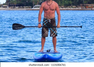 Attractive young man stand up paddle surfing