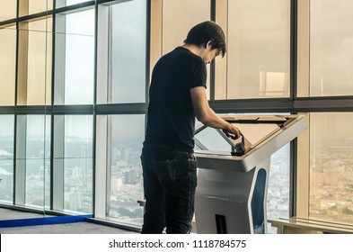 Attractive young man standing front big digital screen with basic tower map data, male touching sensitive display of modern smart building stop for check her location.