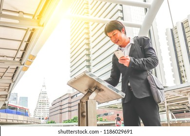 Attractive young man standing front big digital screen with basic tower map data with mobile, male touching sensitive display of modern smart building stop for check her location.