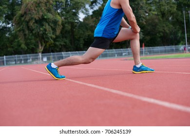 Attractive young man stretching on track before running ,copy space
