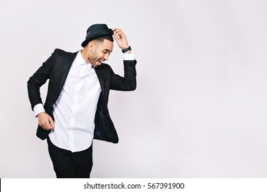 Attractive young man in suit dancing, having fun on white background. Stylish outlook, hat, successful businessman, happy, expressing true positive emotions, funny. Place for text