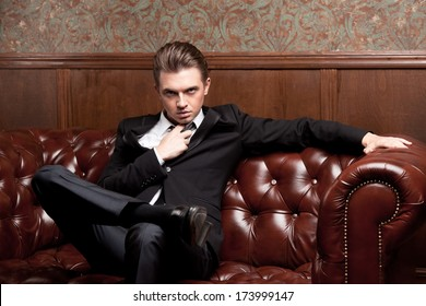 attractive young man in a suit sitting on a retro couch