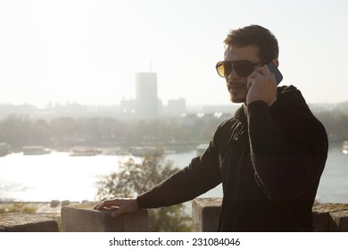 Attractive Young Man With SunGlasses Talking On Mobile Phone Outdoor
