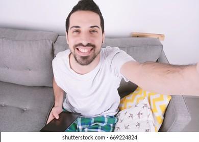 Attractive young man taking selfie. Indoors.