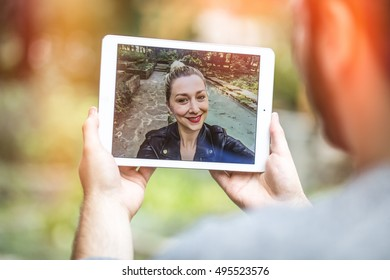 attractive young man talking to his long distance girlfriend on a video call, using a tablet outdoors. graded with a flare.