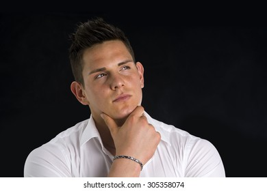 Attractive young man thinking, looking up with hand on his chin, isolated on black background