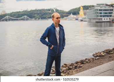 Attractive young man in urban and modern background with casual look walking near the river