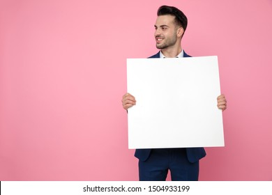 attractive young man wearing navy blue suit, holding an empty board, smiling and looking to side, standing on pink background in studio