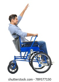 Attractive young man in wheelchair on white background