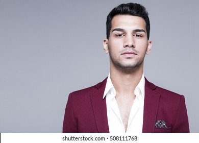 Attractive young man in white shirt and maroon suits studio shot, male model on dark grey background