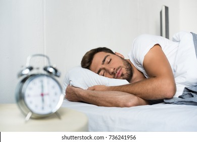 Attractive young man in white t-shirt sleeping in bed with alarm clock on his bedside table