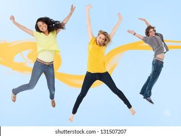 Attractive young man and women jumping for joy with yellow smoke trail on blue background