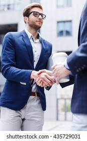 Attractive young men are greeting with handshake