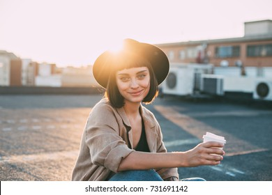 Attractive young millennial student or fashion model in hipster outfit poses for camera on top of rooftop with sun light leaks, smiles and holds coffee cup.