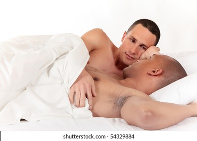Attractive young mixed ethnicity gay, homosexual couple, Caucasian and African American men in the bedroom, grooming.  Studio, white background.