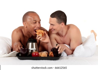 Attractive young mixed ethnicity gay, homosexual couple, Caucasian and African American men in the bedroom, grooming, enjoying breakfast.  Studio, white background.