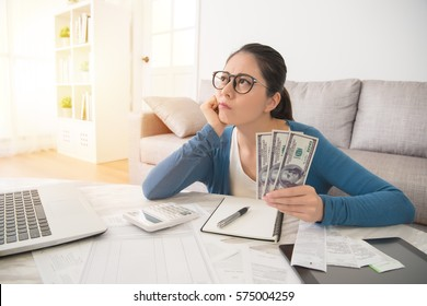 Attractive young mixed race asian woman working on finances worried about the expend cost sitting on sofa in the living room at home. interior and domestic housework concept.