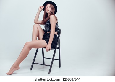 Attractive young model with beautiful make-up and hair-do in stylish black hat and black clothes posing with a chair on a white studio background. Long legs, brown hair, white cyclorama, fashion.