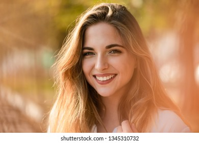 Attractive young model with big bright smile, flare effect.