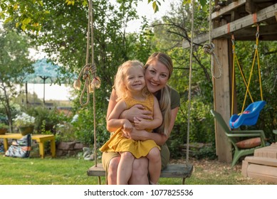 Attractive young mom and daughter on a swing playing in the backyard on a summer day