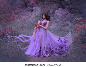 attractive young mother with dark wavy hair and her little daughter, standing together in the forest in amazing long fluttering flying lilac dresses, woman embraces, gently smiles, art family photo