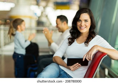 attractive young mother holding tablet computer at airport while waiting for their flight