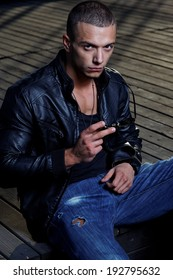 Attractive young muscle male model posing outdoors in black shirt and  leather jacket  .Fashion colors