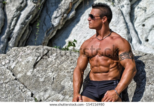 Attractive young muscle man shirtless against white rocks, looking to a side. Large copy-space