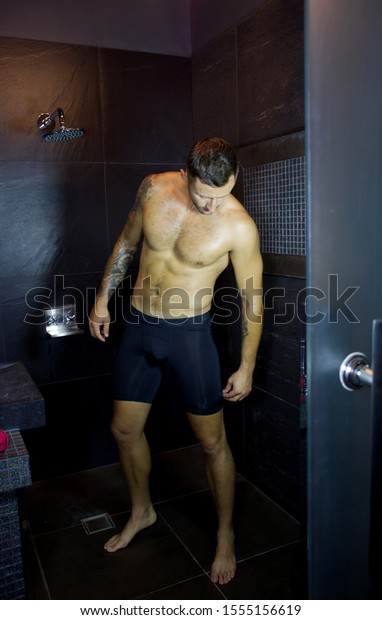 Attractive young muscular man before taking shower in dark tiled bathroom.