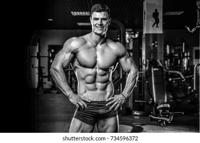 Attractive young muscular sexy Caucasian man of model appearance working out training in the gym gaining weight pumping up muscles and poses fitness and bodybuilding concept