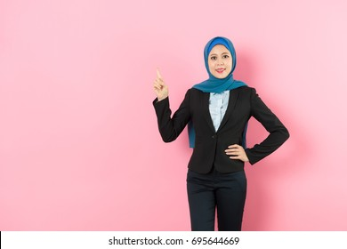attractive young muslim female office worker showing pointing gesture standing in pink background and looking at camera smiling.