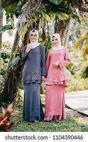 Attractive young Muslim girls wearing baju kurung with hijab.Hijab fashion portraiture.Muslim girl fashion for Kid ul Fitr celebration.Modern muslim girl with hijab.