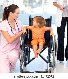 Attractive young nurse talking to a baby in a wheelchair