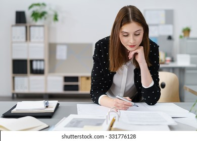 Attractive Young Office Woman Working on the Business Papers While Leaning on her Desk.